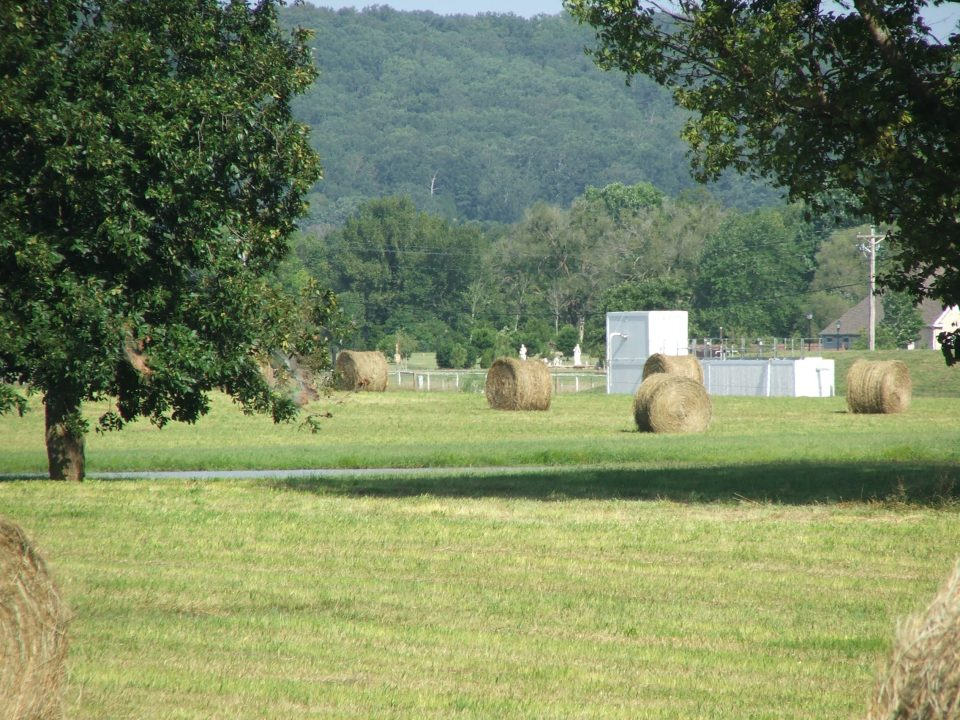 Hay bales in the foreground with wastewater treatment plant in the background,