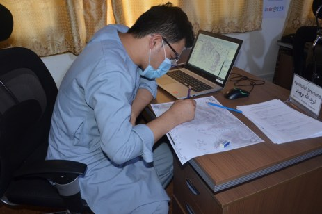 A participant working how to analyze risk areas on the contour map during the session on 'DRR Analysis'.