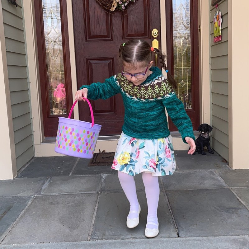 a little girl donning a hand knitted sweater and flower dresshops off the front steps of a house in search of Easter eggs