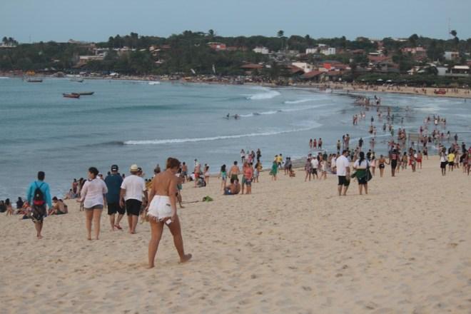 Turistas descendo a duna do Pôr do sol