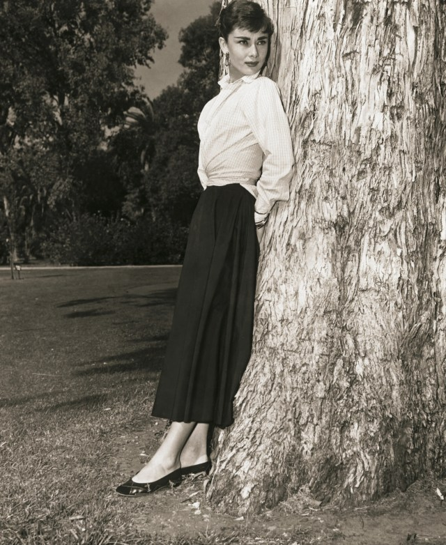 L'attrice di origine belga Audrey Hepburn (1929-1993) appoggiata a un albero in un foto pubblicitaria del 1950 circa