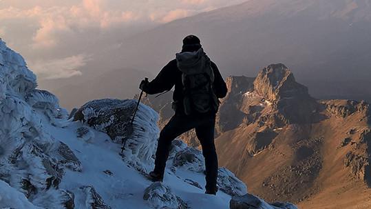 Seorang pria mendaki ke puncak gunung.