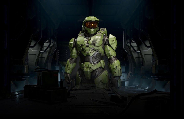 """Halo Infinite. Master Chief, de pie, en una habitación con poca luz, la parte delantera de su armadura está ligeramente dañada debajo del """"117"""" en el pecho."""