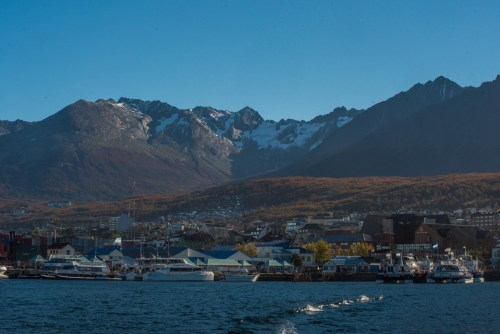View of Ushuaia town from the water and glaciers above it