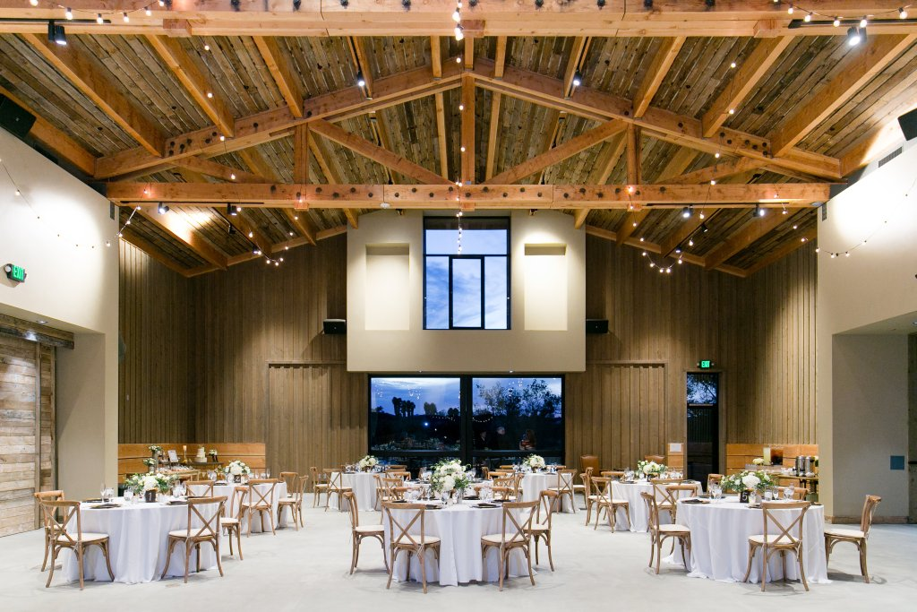 Indoor barn style reception with twinkle lights and high ceilings with cross back chairs at Temecula wedding at wedgewood galway downs wedding venue