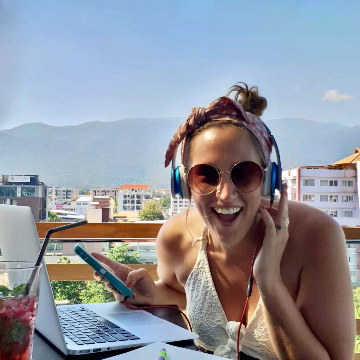 woman with headphones and sunglasses looking into camera, holding mobile phone