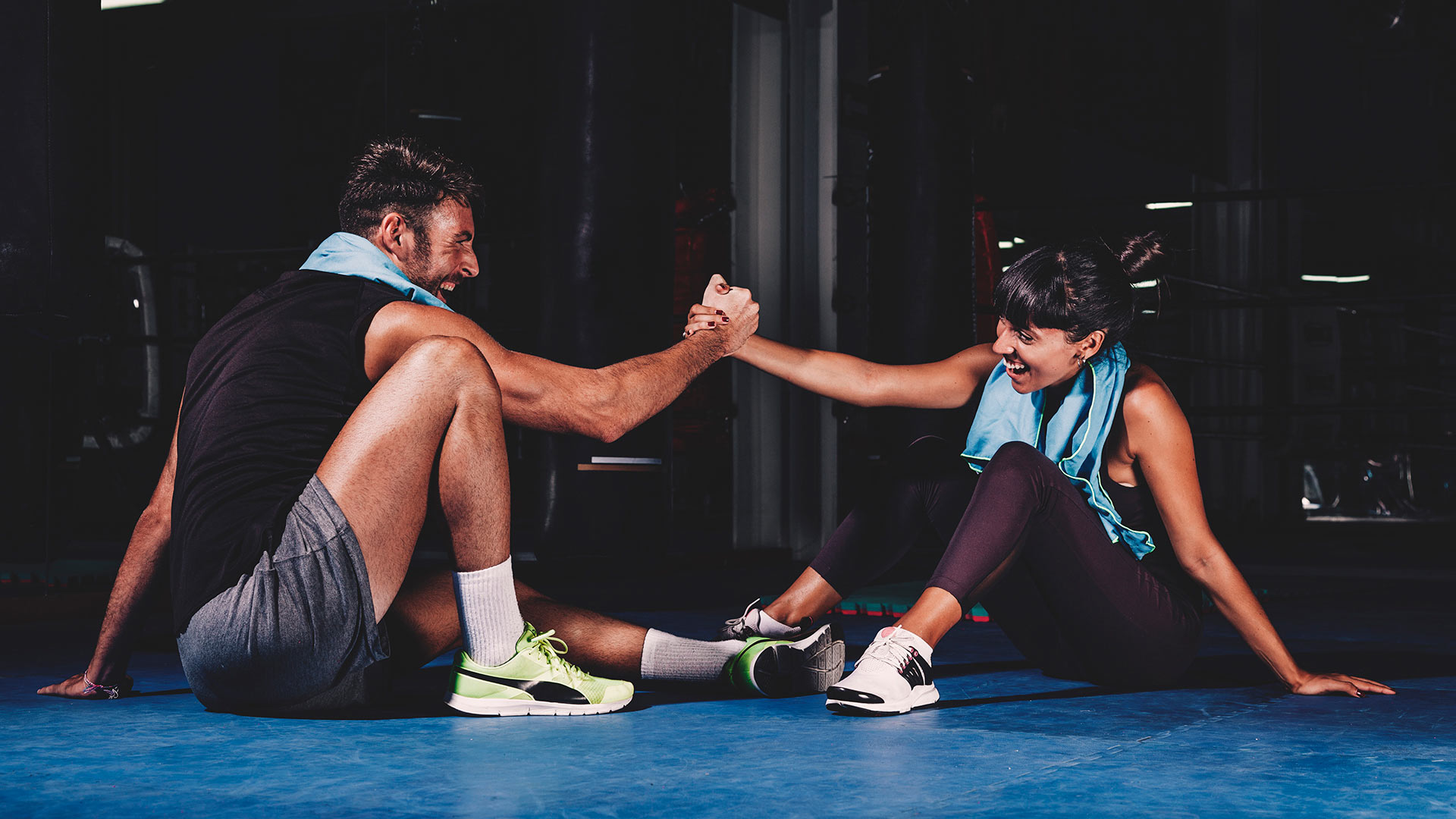 Man and Woman couple at the gym sitting on workout mats, clasping hands and laughing