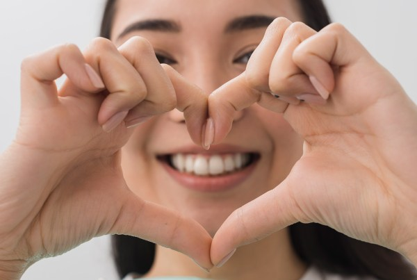 Woman smiling while making a heart with her hands in front of her face