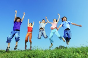 Group of five happy children jumping outdoors.