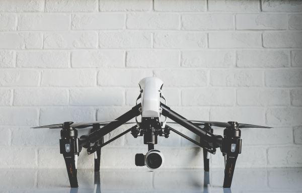 white drone against white brick wall