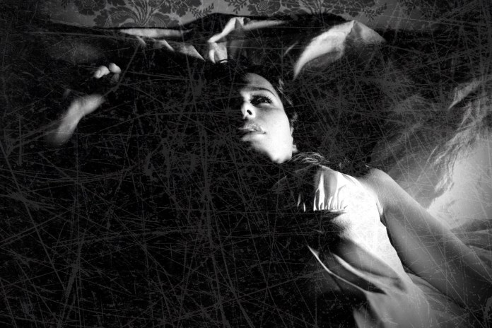 A woman lies in bed awake in a black-and-white photo.