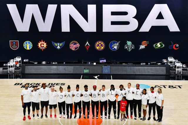 Mystics players stand in a row wearing shirts that spell out Jacob Blake's name, flanked by people in shirts that read