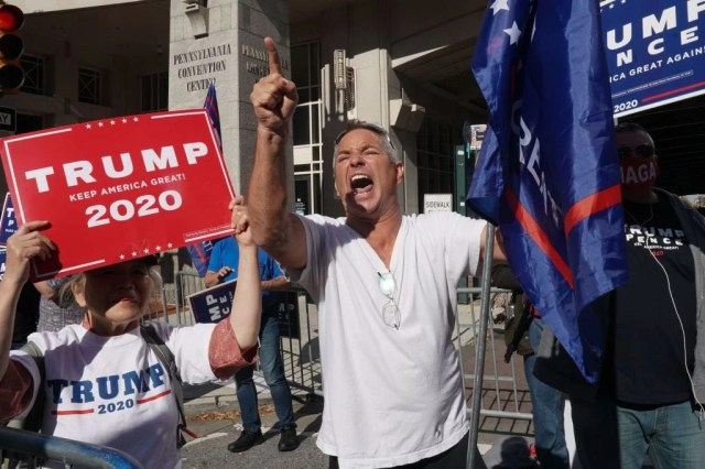 An angry middle-aged white man holding a Trump flag shouts and points his finger amid other Trump supporters holding up Trump signs.