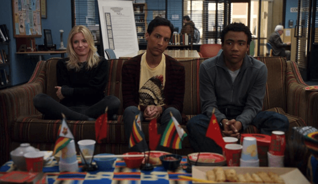 Gillian Jacobs, Danny Pudi, and Donald Glover sit on a couch, staring a table full of small Chinese and Ghanian flags.