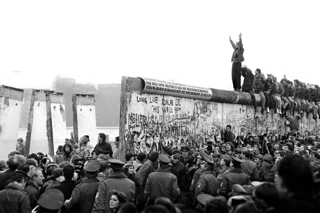 People crowd around and stand on the Berlin Wall with parts of it broken down.