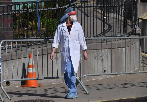 A doctor walking down the street in a face shield and lab coat, looking like a character out of Star Wars.