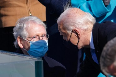 Joe Biden leans in to speak to Mitch McConnell, who is sitting and wearing a mask.