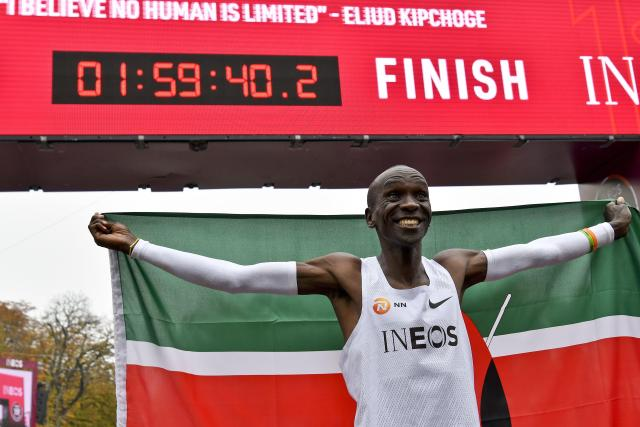 Kenya's Eliud Kipchoge celebrates after busting the mythical two-hour barrier for the marathon on October 12, 2019 in Vienna.