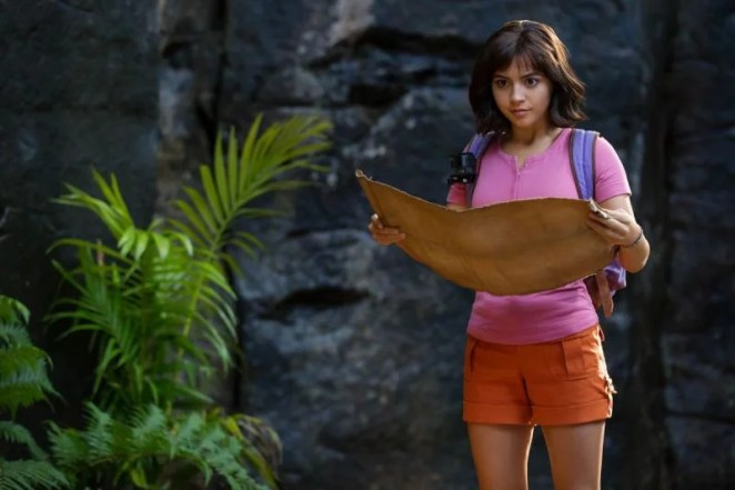 Isabela Moner wears a pink shirt, orange shorts, and a backpack. She holds a map.