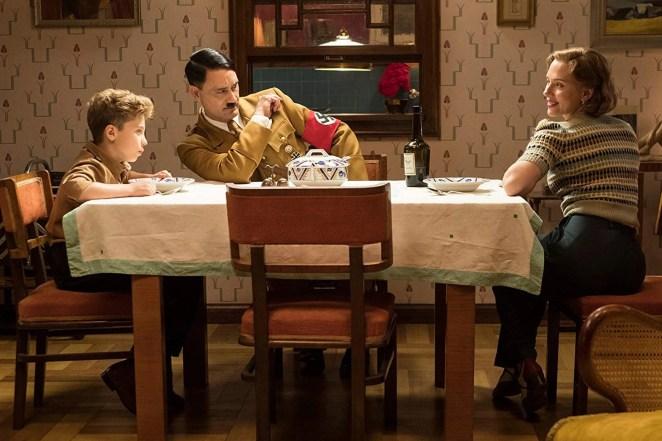 Roman Griffin Davis, Taika Waititi (as Hitler), and Scarlett Johansson sit around a table.
