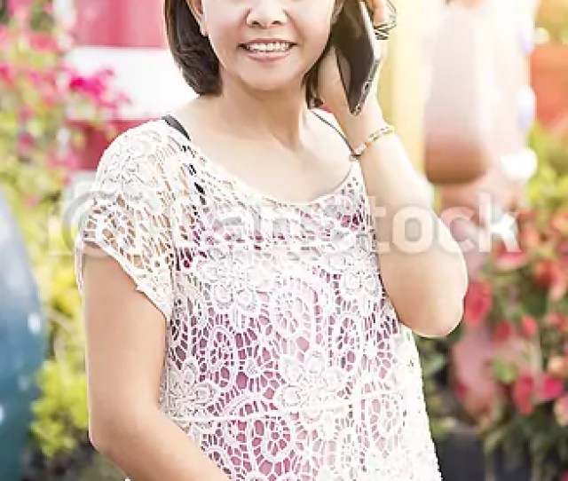 Attractive Mature Asian Woman Phoning At Home In Garden Csp39820233