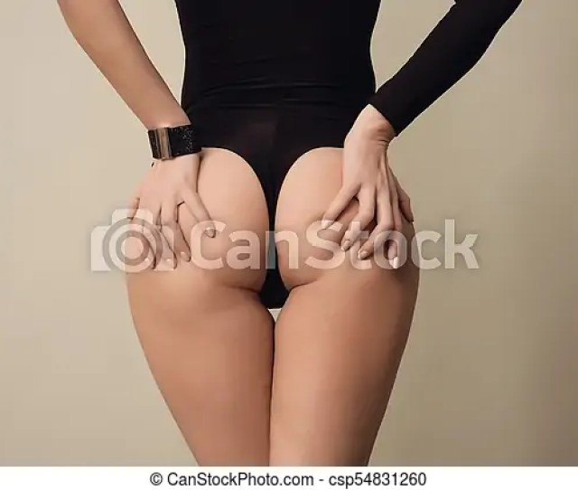 Athletic Young Woman In A Black Bodysuit Standing Back And Holding Hands Himself For A Nice Juicy Ass On Background