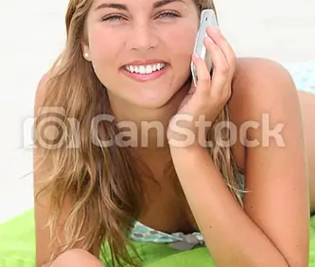 Blond Teenager Laying On A Beach Whilst Making A Call Csp8769333