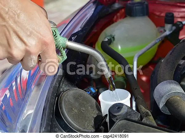 Closeup of a young man filling the tank of windshield washer fluid of a car with a hosepipe.