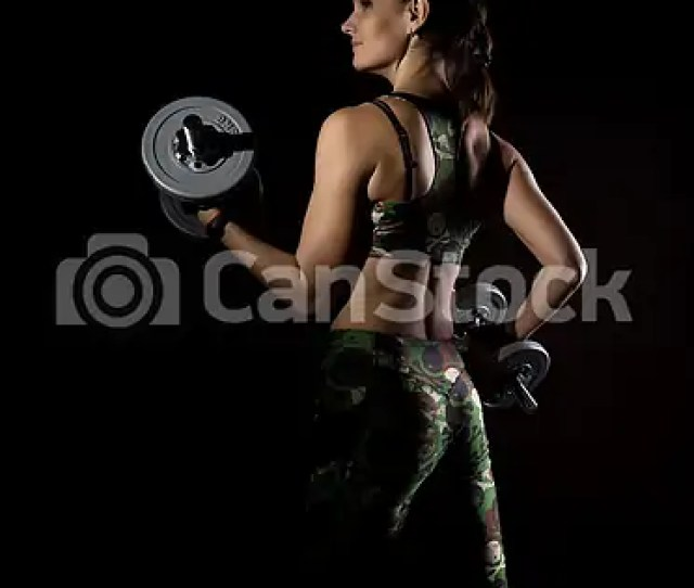 Fitness Sexy Girl With Dumbbells On A Dark Background Athlete Doing Exercises In The Gym