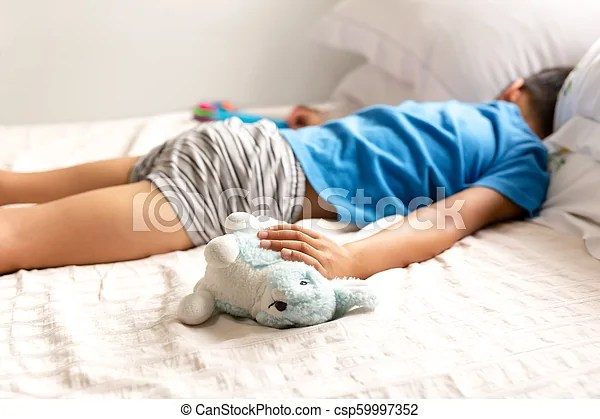 https www canstockphoto com little boy sleeping in bed and holding 59997352 html