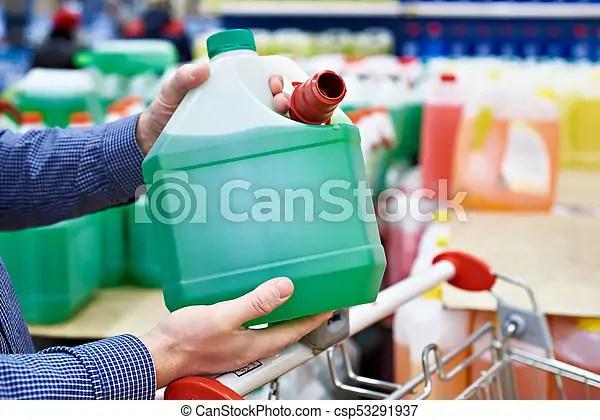 Man buys windshield washer fluid in shop. Man buys windshield washer fluid in the supermarket.