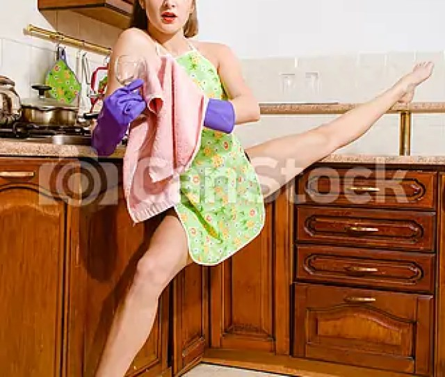 Young Beautiful Super Flexible Woman Pinup Girl Wiping Glass In Purple Gloves At The Kitchen With