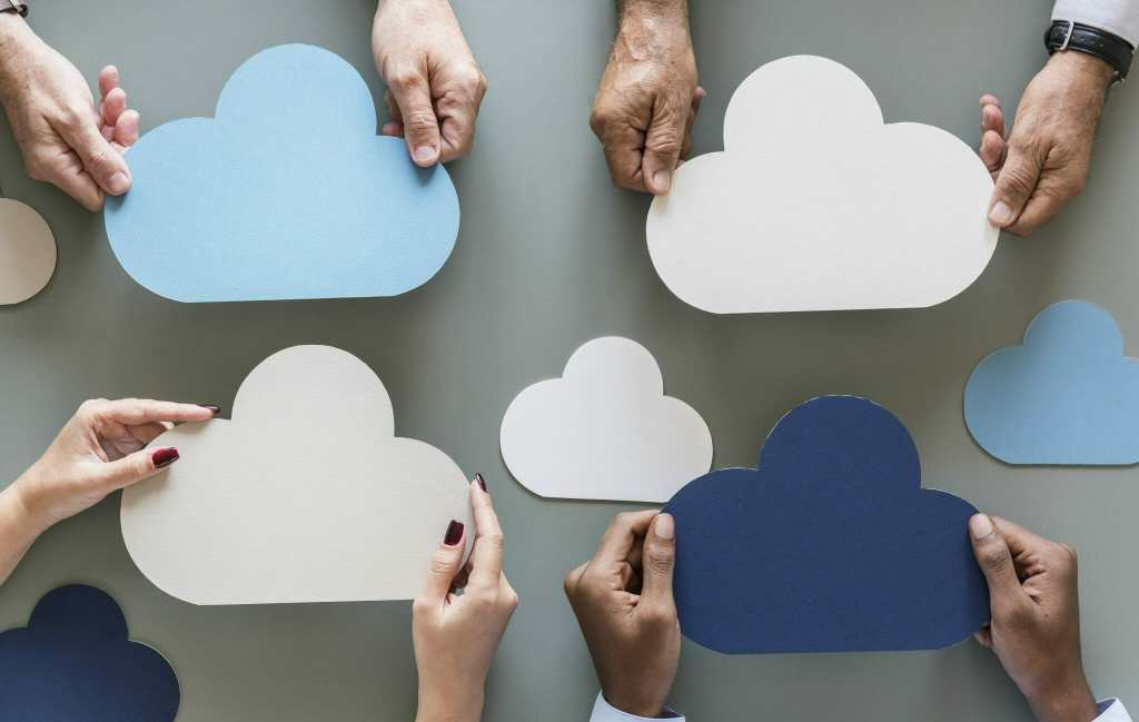 Hands holding cloud cutouts over gray background as imagery for cloud computing