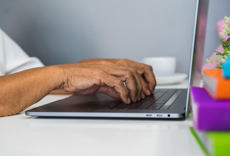 elder person typing on their laptop