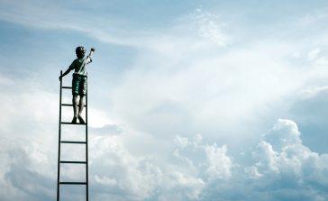 enfant grimpant sur une échelle pour atteindre le ciel