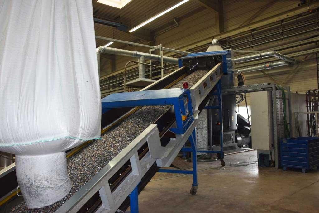 Neue Kunststoff-Recyclinganlage Erema mit Mahlgut auf Förderband