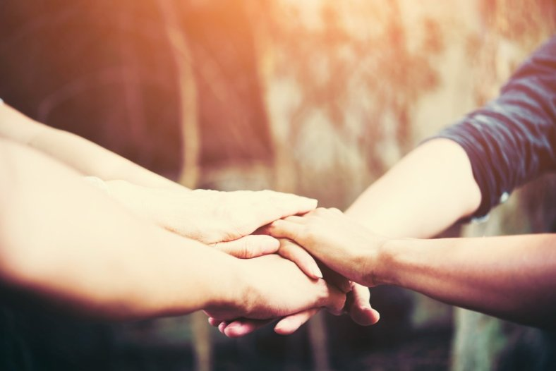 Dos personas dándose la mano, ofreciendo ayuda
