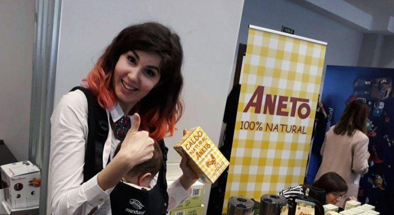 Chucherías, bloguera en stand de Aneto con caldo en la mano y haciendo el gesto de validación con la mano