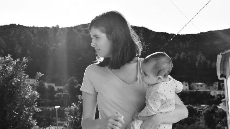 Foto en blanco y negro de madre sujetando a su bebé en brazos, maternidades de colores