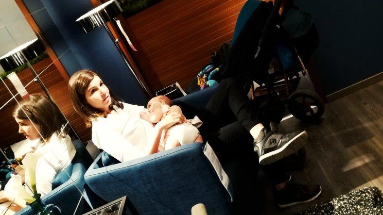 Madre dando el pecho en público, sentada en un sillón de una exposición de Ikea a un bebé de un año