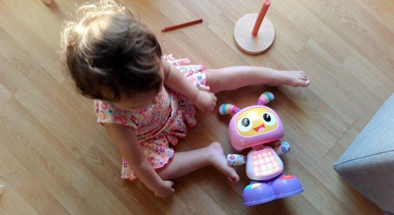 Foto para post Yo también lo sello, bebé con vestido de flores sentada jugando con Robita Robotita de Fisher Price