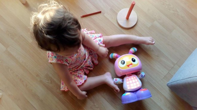 Foto para post Yo también lo sello, bebé de un año con vestido de flores sentada jugando con Robita Robotita de Fisher Price
