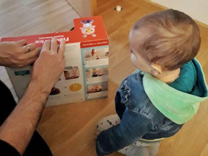 Niña y padre abriendo la caja de Robita Robotita de Fisher Price