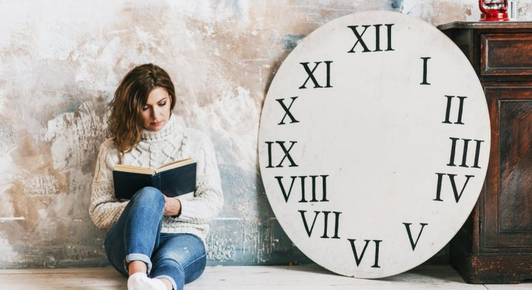 Mujer leyendo sentada en el suelo al lado de un reloj gigante sin agujas que simboliza el reloj biológico que no se encendió nunca