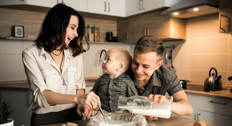 Familia de padre, madre e hijo felices jugando en la cocina, para representar el tema de permisos por maternidad y paternidad