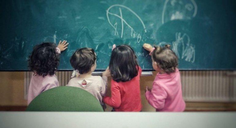 4 niñas pintando en una pizarra, evocando la adaptación a la escuela infantil