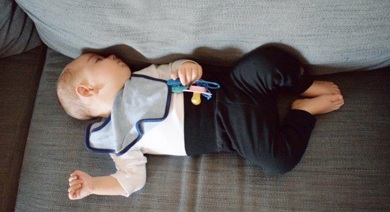 Foto para pesadillas o terrores nocturnos, bebé durmiendo en un sofá, con chupete y babero