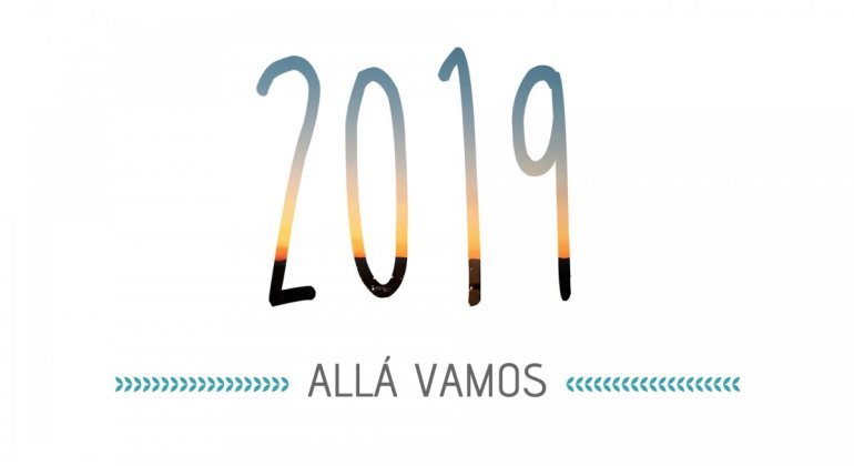 Portada para el post propósitos de año nuevo, fondo blanco con 2019 recortado sobre fondo de atardecer y el lema Allá vamos