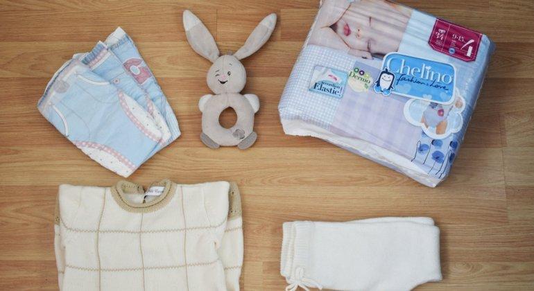 Foto cenital de paquete de pañales chelino, con dos pañales de la marca, un sonajero peluche de un conejito, y un conjunto de punto en color crudo