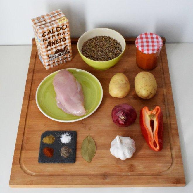 Ingredientes para receta tradicional de lentejas con caldo aneto de puchero con cuenco de lentejas, plato con pollo y otros ingredientes sobre tabla de madera